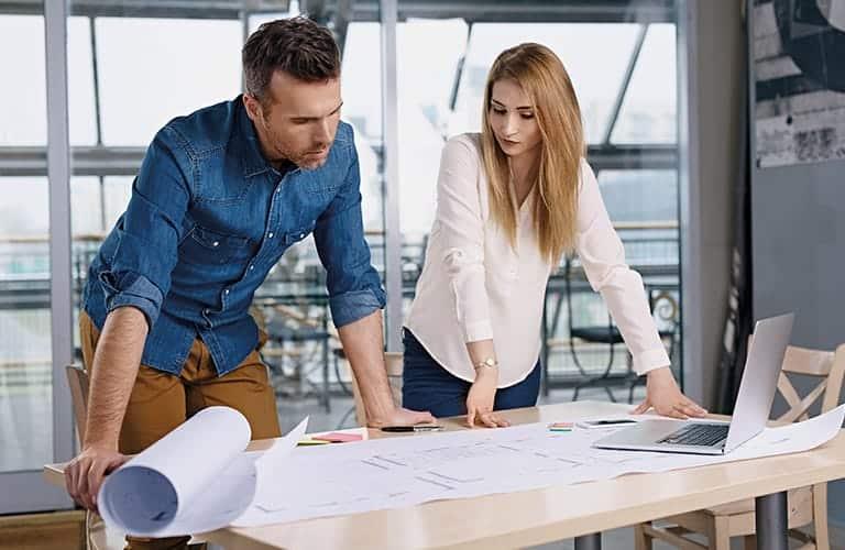 Une femme et un homme debout travaillant sur plans