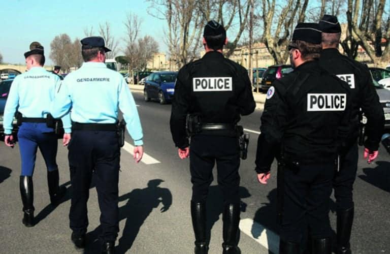 Gendarmes et policiers de dos marchant sur la voie publique